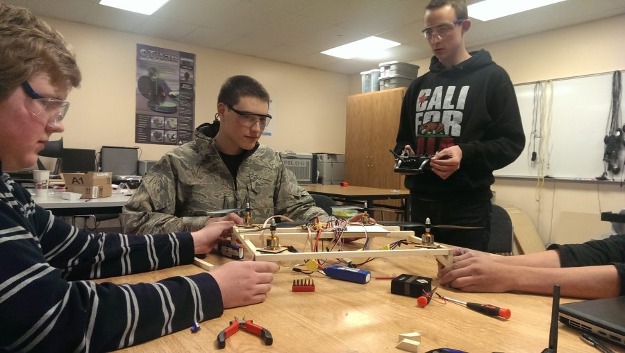 Several students gather around for the first test run of their quadcopter. After a bit of tinkering, the motor finally whirs and the blades begin to spin.