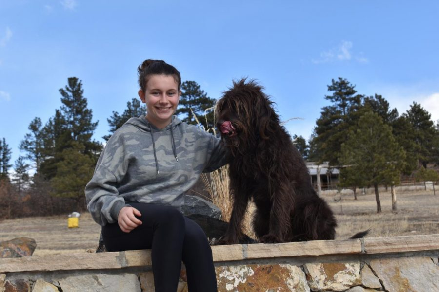 """Madi Farley, a football manager for CV, poses with her dog, Sloperdale, on a March morning. She has been passionate about the game since she was little. """"It's something my dad and I shared when I was little,"""" Farley said. """"I love the game."""""""
